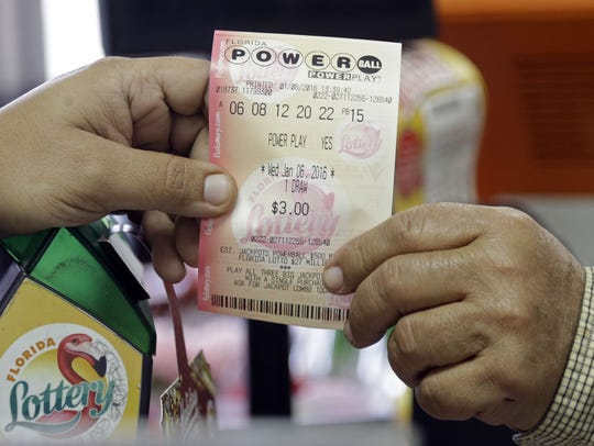 A clerk hands over a Powerball ticket to a customer in Hialeah, Fla. in this file photo.