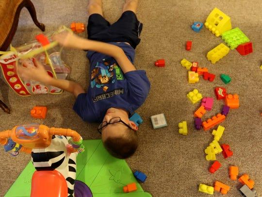 Jordan Tellekson, 11, plays on the floor at the Tellekson
