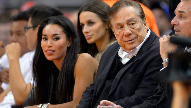 """In this photo taken on Friday, Oct. 25, 2013, Los Angeles Clippers owner Donald Sterling, right, and V. Stiviano, left, watch the Clippers play the Sacramento Kings during the first half of an NBA basketball game in Los Angeles. The NBA is investigating a report of an audio recording in which a man purported to be Sterling makes racist remarks while speaking to his Stiviano.  NBA spokesman Mike Bass said in a statement Saturday, April 26, 2014, that the league is in the process of authenticating the validity of the recording posted on TMZ's website. Bass called the comments """"disturbing and offensive.""""  (AP Photo/Mark J. Terrill) ORG XMIT: CAMT108"""