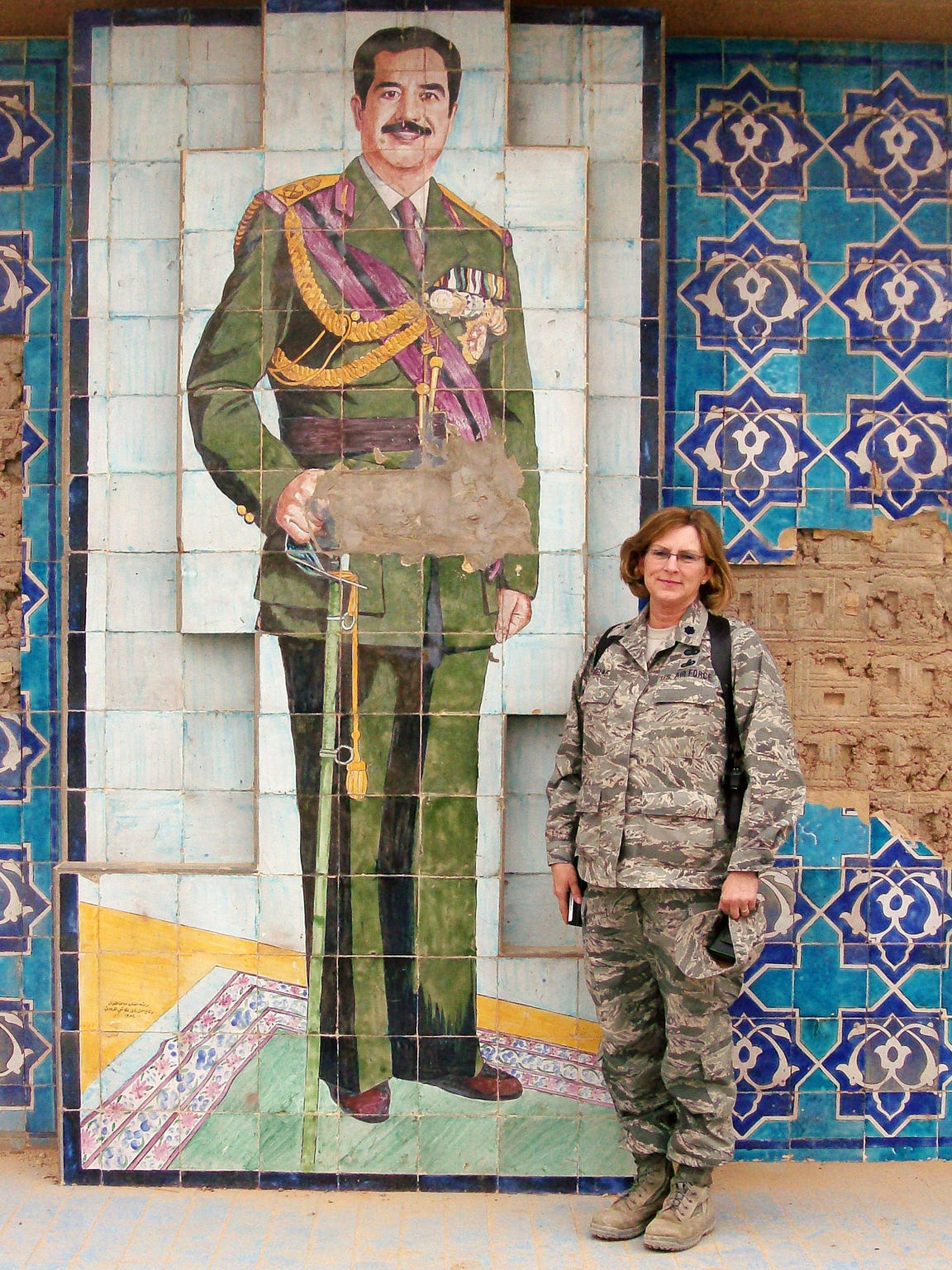 Tami Mielke is shown in front of a mural of Saddam Hussein during her deployment in Iraq.