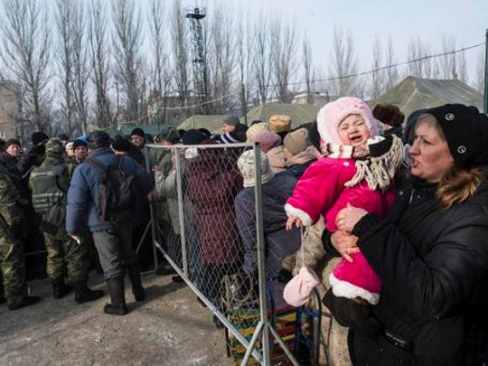 A baby girl cries in her mother's arms as they stand in queue to get humanitarian aid at the humanitarian aid center in Avdiivka, eastern Ukraine, Friday, Feb. 3, 2017. Strong shelling hit both government- and rebel-controlled areas of eastern Ukraine in a continued escalation of the country's fighting.
