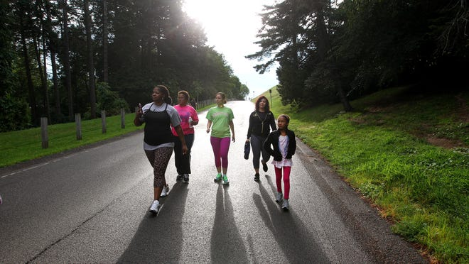 Lisa Medina (second from right) leads a walking group from her church, Joint Heirs Kingdom Ministries, around Cobbs Hill Reservoir. The others in the group include (left to right) Sytraina Gause, Mona Isler, Denise Esters and Lisa's daughter Anajah, 8. Lisa is trying to help people live healthier lives.