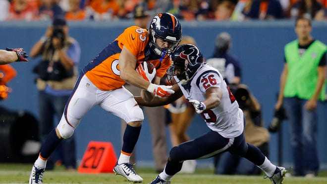 Denver Broncos wide receiver Wes Welker (83) is hit by Houston Texans defensive back Brandon Harris (26) during the first half of an NFL preseason football game, Saturday, Aug. 23, 2014, in Denver.