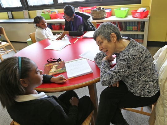 Volunteer Corinne Umphrey (right) and Jada Giles join other groups reading together at IPS School #56.