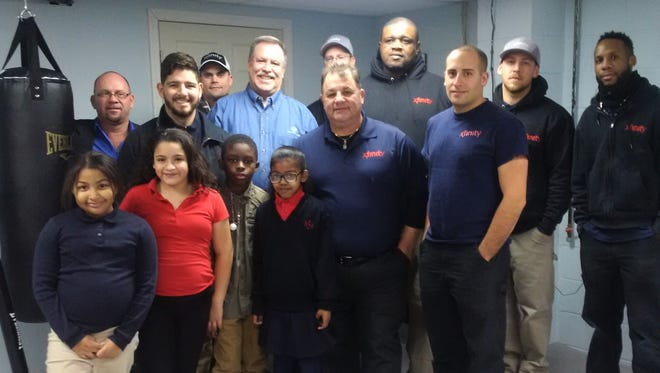 Several Comcast technicians held a fundraiser to support the Boys and Girls Club of Vineland. (Back row, from left) Angel Rivera, Club counselor Eliud Rivera, Chris Totton, Club director Chris Volker, Pete Knoff, Charles Jones, Nick Montgomery, Justin Rocker; and (front row, from left) Club members Marliena Mercado, Yanelis Andeliz, Johnathan Brown, Mariah Shievdayal, and Deber and Franco Lombardi are pictured at the club. Comcast technicians Luis Rosado, Harry Behrens, Bill Rivera and Gary Guadalupe are not pictured.