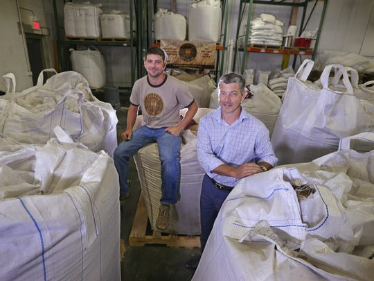 One-ton totes of different malting grain varieties surround Adam Filippetti, founder and maltster, and his brother, Paolo Filippetti, founder and president, at Pioneer Malting Inc. in Chili.