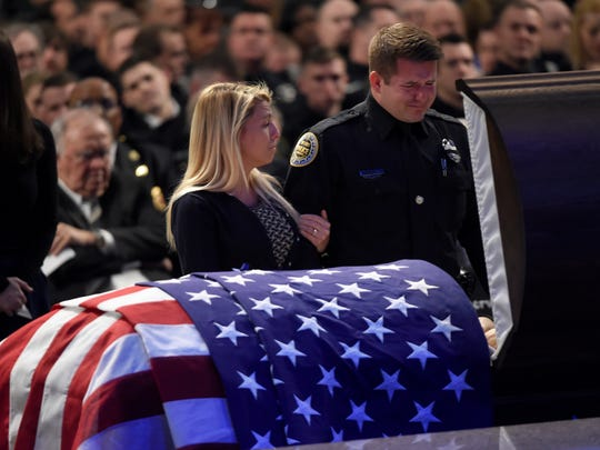 Mourners stand at the casket of fallen Metro police