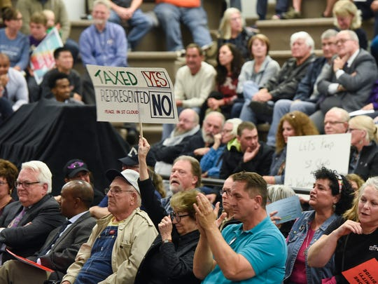 People hold signs during a St. Cloud City Council discussion on moratoriums related to refugee resettlement Monday, Oct. 23, at City Council chambers.