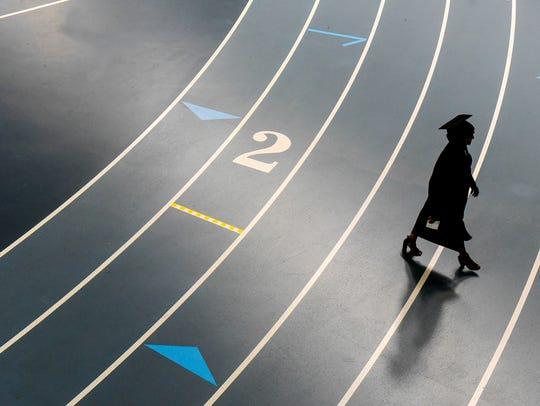 A graduate walks toward St. Cloud Tech graduation ceremonies