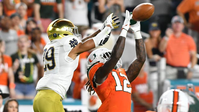 Nov 11, 2017; Miami Gardens, FL, USA; Miami Hurricanes cornerback Malek Young (12) breaks up a pass intended for Notre Dame Fighting Irish wide receiver Kevin Stepherson (29) in the second quarter at Hard Rock Stadium. Mandatory Credit: Matt Cashore-USA TODAY Sports