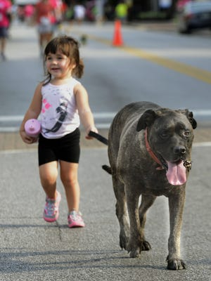 """Sophia Goodyear, 2, walks """"Zoe"""" along Palafox Pl.  Saturday during Paws on Palafox, the events proceeds went to the Pensacola Humane Society Barbara Grice Memorial Spay and Neuter Clinic."""