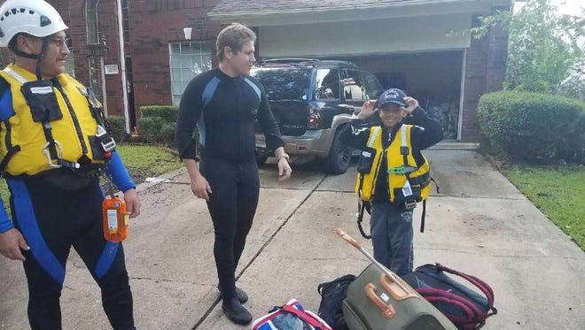 Las Cruces Fire Department Lt. Joe Leos and driver/operator Jeremy Eckhart are with a young flood victim under evacuation orders in Texas.