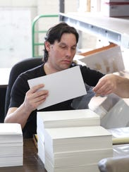 Christian Hatrak places comics and cardboard backing