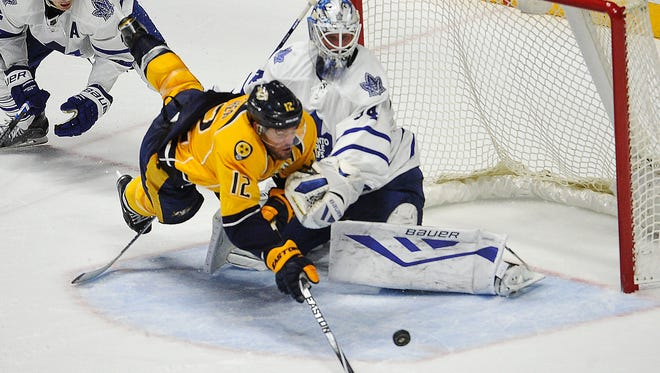 Predators center Mike Fisher (12) goes airborne as he takes a shot against Maple Leafs goaltender James Reimer on Thursday.