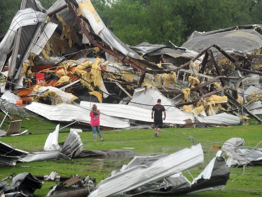 A man and woman examine the twisted wreckage of Glass Masters on U.S. 49 Frontage Road in Richland shortly after it was destroyed by a tornado late Monday afternoon.