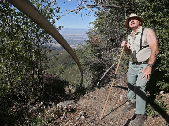 Retired Forest Service employee Gary Earney stands next to Nestle's water pipeline in the San Bernardino National Forest.