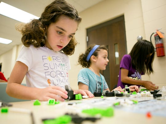 Jenna Bseiso, 7, from left, Fiona Neal, 7, and Kairi Kim, 10, work on building cars Monday during the Pullback Car Frenzy at University of Wisconsin-Marshfield/Wood County. The camp was one of two youth Science, Technology, Engineering and Math camps being offered at UW-M/WC this week.
