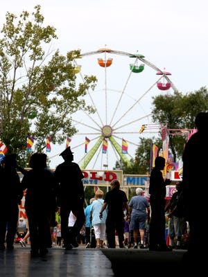 With part of the midway behind them including the 95 foot tall ferris wheel, people walk in and out of the inside of the Michigan State Fair on the grounds of the Suburban Collection Showplace in Novi, Michigan on Friday, Aug. 29, 2014. Eric Seals/Detroit Free Press