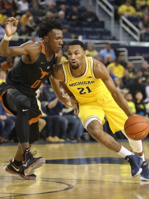 Michigan guard Zak Irvin drives against Texas guard Tevin Mack during the first half Tuesday at Crisler Center.