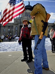 Trey Cathey of Yellowstone County carries his .30 caliber semi-automatic rifle as he talks with John Richardson during the Lewis and Clark Conservative Tea Party's Constitution Rally on the steps of the Sate Capitol.
