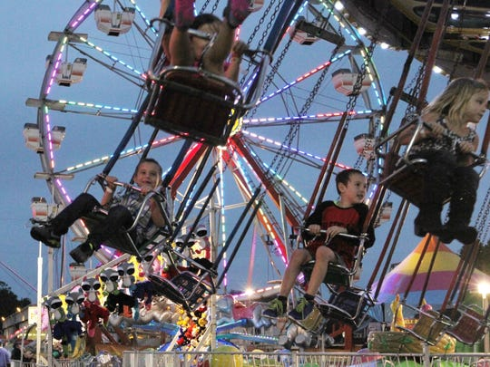 Children ride the swings at the Southwest Florida and Lee County Fair on Thursday night at the Lee County Civic Center.