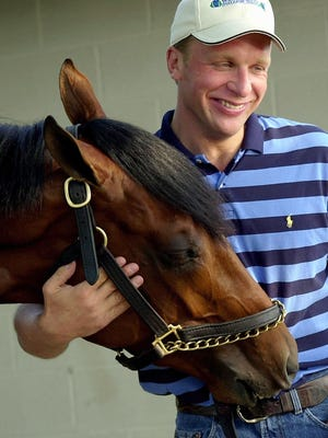 Former trainer Simon Bray holds his Kentucky Derby hopeful, Startac, after morning workouts on May 4, 2001, at Churchill Downs.