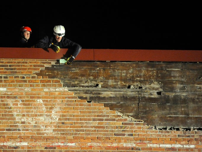Fire department crews respond to bricks falling from the top of the Larson Square building at 600 N. Main Avenue in Sioux Falls, S.D., Tuesday, Aug. 26, 2014.