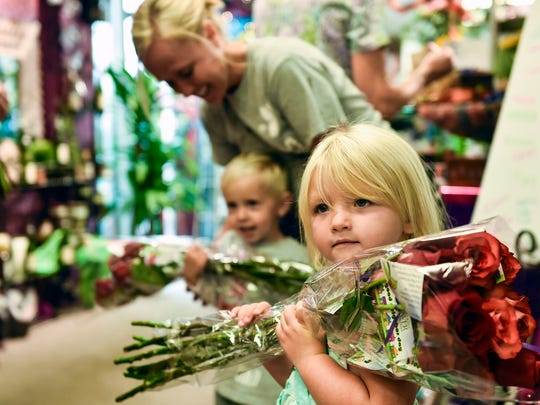 Three-year-old Sawyer Curts clutches her dozen roses closely as she waits to leave the Marion Flower Shop and get busy handing out the flowers to people in the community. Sawyer and her mother Tara Hines-Curts took part in the Marion Flower Shop's Good Neighbor Day on Wednesday.