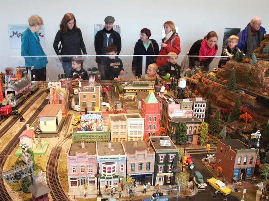 Visitors check out the Mega Model Trains exhibit at the Morris Museum. The display is 288 square feet and contains 500 feet of track, 125 miniature buildings, and 160 cars and trucks. The trains  blow their whistles past a replica of Morris Plains.