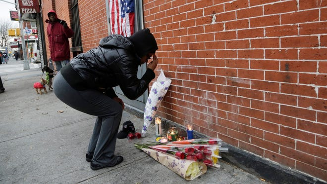 Maria Alomar genuflects  Dec. 21 at a makeshift memorial for two police officers who were shot Saturday in New York.
