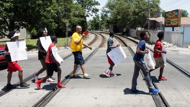 Participants in the Walk the West End Against Violence near the end of their journey as they cross railroad tracks at 28th & Wilson on Saturday. 6/10/17