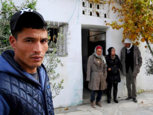 The brother of fugitive Tunisian extremist suspected in Berlin's deadly Christmas market attack, Walid Amri , poses for a photo in front of the family house where Anis Amri used to live, in Oueslatia, central Tunisia, Thursday, Dec. 22, 2016. Amri's family members, speaking from his hometown, were shaken to learn he's the prime suspect in Monday's rampage, which killed 12.