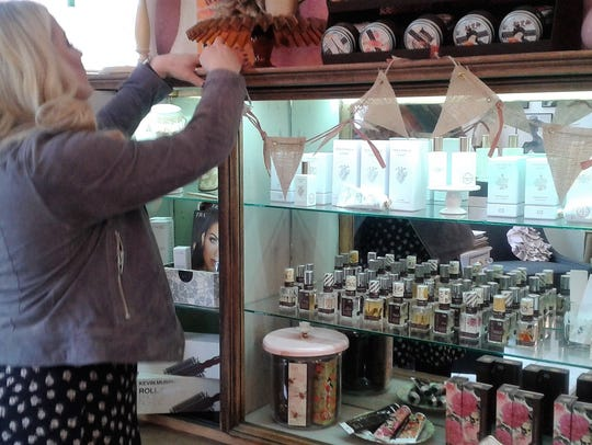 Salon owner Laura Roberts works on a display at Posh
