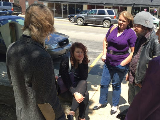 Nicole Vannatter, seated, listens as friends of her brother Raul Turrieta tell stories about him Tuesday outside the Marion County Courthouse. Vannatter, of Denver, is attending the trial of Christina Scroggin who is accused of murder in Turrieta's April 2, 2013 shooting death.