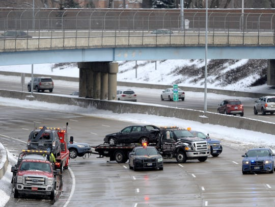 Police and tow trucks clean up after a serious vehicle accident that closed westbound I-696, west of Dequindre in Madison Heights, Dec. 25 2017.