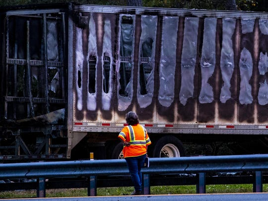 In this Thursday, Jan. 3, 2019, file photo, a worker looks at a charred semitrailer after a wreck with multiple fatalities on Interstate 75, south of Alachua, near Gainesville, Fla.