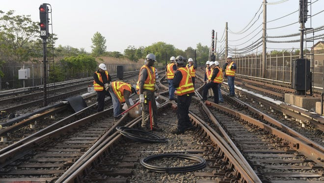 Workers repair a section of cable that was severed by vandals who stole 500 feet of copper cable from train tracks along the A train subway line south of Howard Beach, in the Queens borough of New York. The crime forced the MTA to suspend train service entirely in the area and replace it with shuttle buses.