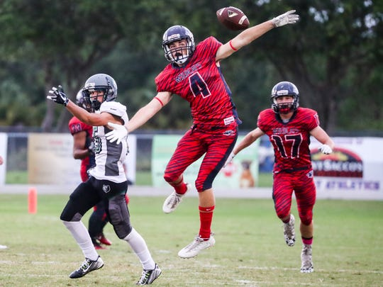 Estero's Colin Simoneau reaches back for the ball after the pass intended for Vladimir Faugue was broke up. Palmetto Ridge played at Estero Tuesday night.