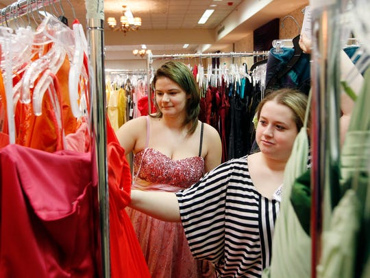 Breanna Blaszak, 14, of Irondequoit, left, looks for dresses with the assistance of Katelyn Thompson, 17, of Webster at the Prom Fair.