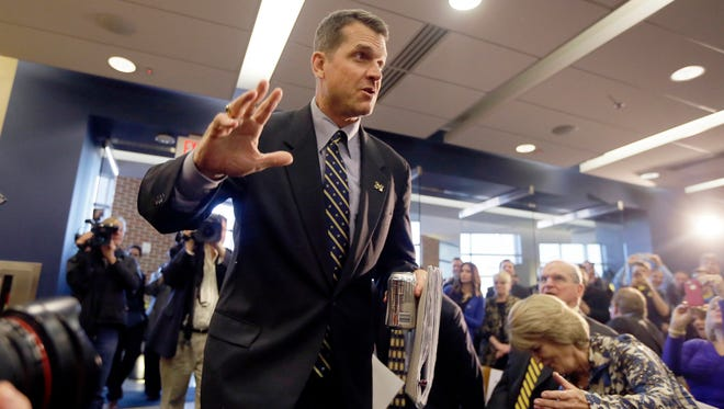 Jim Harbaugh, Michigan's new football coach, arrives for a news conference Dec. 30, 2014, in Ann Arbor.