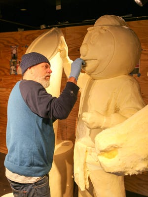 Sculptor Paul Brooke, from Cincinnati, puts the finishing touches on Ohio State mascot Brutus Buckeye, featured at the 2015 Ohio State Fair.
