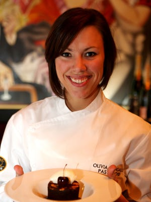Pastry chef Olivia Pangallo of Jeff Ruby's Steakhouse shows her creation, a chocolate almond cake with a cherry bourbon sauce.