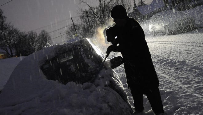 Cold and overexertion can contribute to winter heart attacks. Here, a man removes snow from his car in Catonsville, Md.