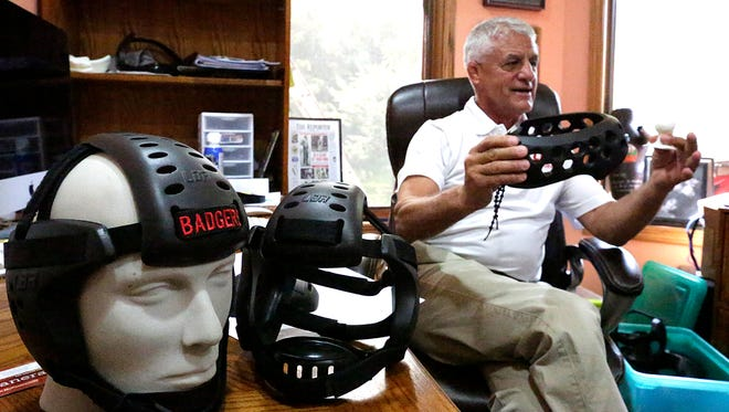 Larry Marchionda, of Fond du Lac, holds up a miniature model and a finished product of soccer headgear in his home office, while a mannequin head sports his company's wrestling headgear on Sept. 2.
