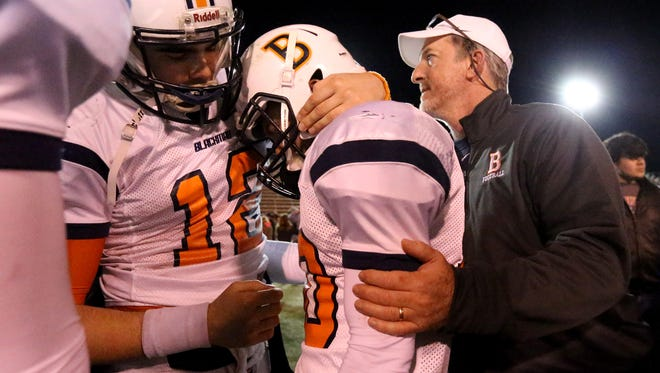 Blackman senior quarterback Miller Armstrong (12), left, comforts senior teammate Blake Taylor (10), center following the Blaze's 42-7 loss to Maryville in a Class 6A state quarterfinal. Far right, Blackman assistant  John McCreary comforts Taylor also.