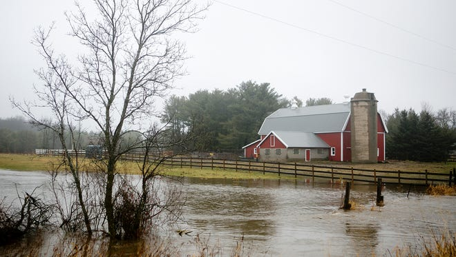 Flooding appears next to a barn off of Highway 66 next to the Wisconsin River near Wisconsin Rapids, Monday, Dec. 14, 2015. The National Weather Service says widespread flooding is not a concern.