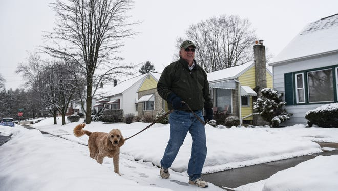 Carl Wilson takes Laci his Golden Doodle for a walk along E. Chestnut St. in Cleona as a snow storm hit the Lebanon Valley on  Tuesday Feb. 9, 2016.