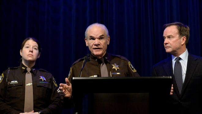 Ingham County Sheriff Gene Wriggelsworth, flanked by  Michigan Attorney General Bill Schuette, and Ingham County Det. Amber Kenny-Hinojosa, speaks at a press conference Monday, March 14, 2016, to discuss charges against Ingham County Prosecutor Stuart Dunnings III. Dunnings is charged with 15 criminal charges in Ingham, Clinton and Ionia counties including pandering and engaging in services of prostitutes.