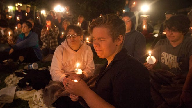 Clark Froelich holds a candle during a candlelight vigil at this year's Transgender Day of Remembrance at A Place of Peace in Ventura.