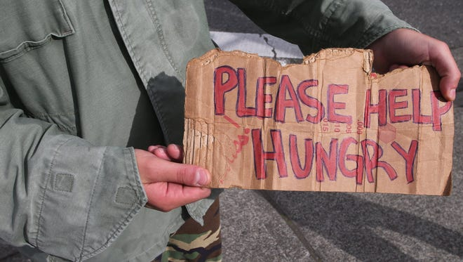 Leroy (last name not given) holds a sign while panhandling in October 2014 at Warren Avenue and Sixth Street in Bremerton.